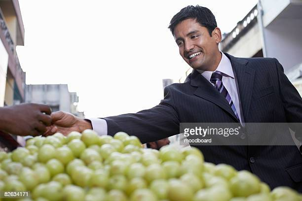 Business man paying fruit merchant, low angle view