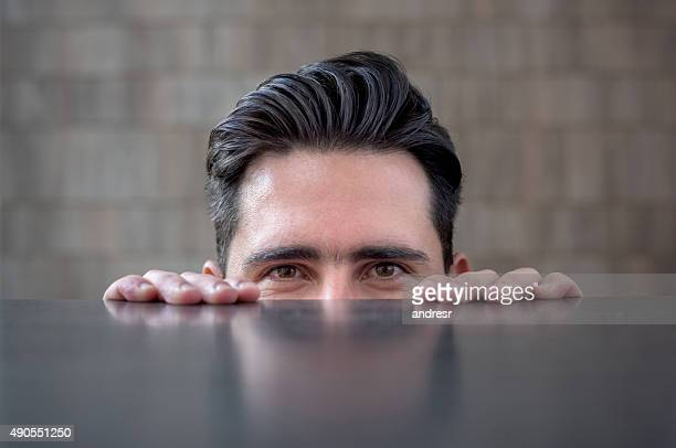 Business man peeking over a table