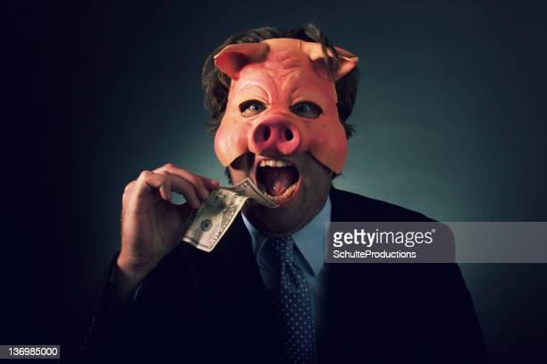 Uomo d'affari mangiare denaro maiale