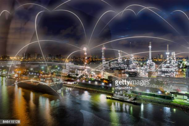 Business man point finger touching network of business connection, Business technology concept with oil refinery industry plant from aerial view in oil industry. Industrial concept.