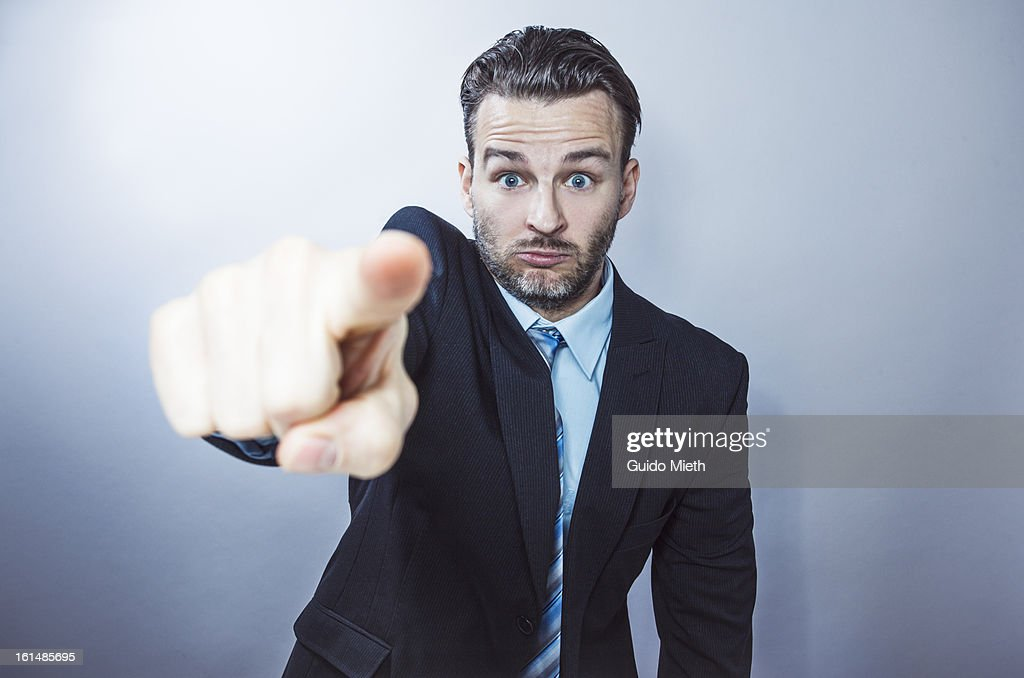 Business man pointing with finger into camera.