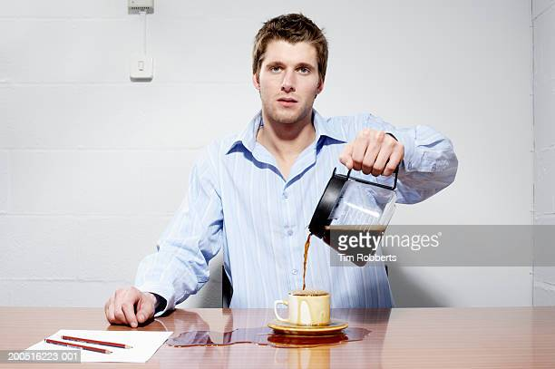 Business man pouring coffee into cup and onto table