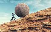 Business man pushing large stone up to mountain.  Success concept. This is a 3d render illustration'n