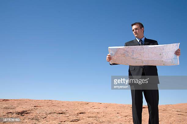 Business man reading a map in desert