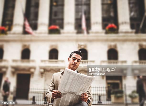 Homme d'affaires, lisant un journal assis sur wall street