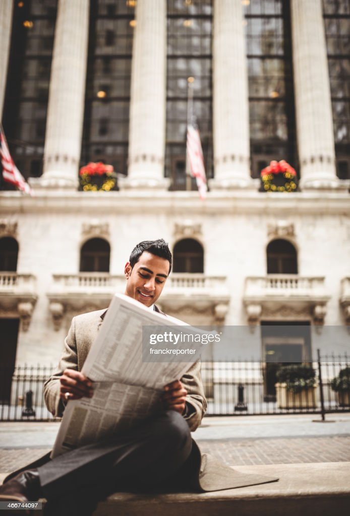 business man reading a newspaper sitting on wall street : Stock Photo