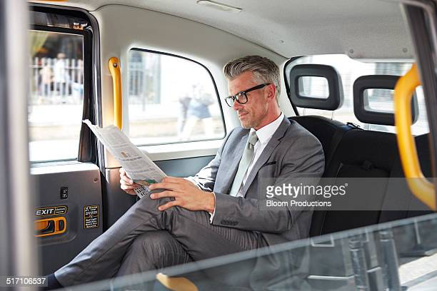 Business man reading a paper in a taxi