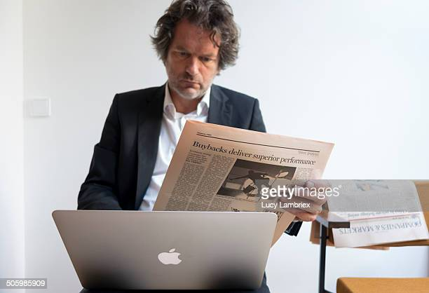 Business man reading Financial Times while looking at his laptop computer