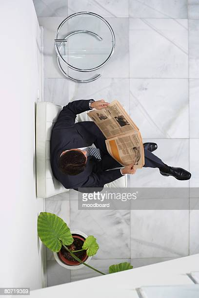 Business man reading newspaper in lobby view from above