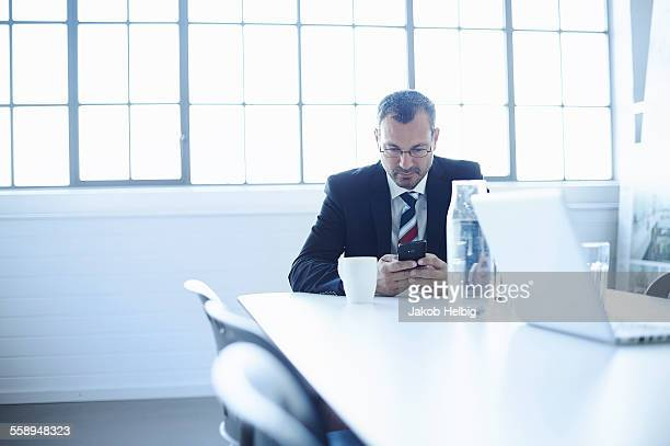 Business man reading smartphone texts at conference table