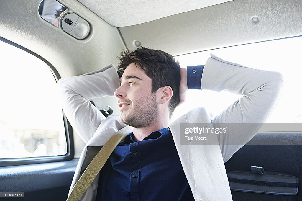 business man relaxing in taxi and smiling