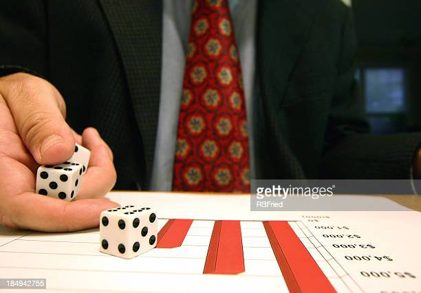A business man rolling dice on a graph of profits