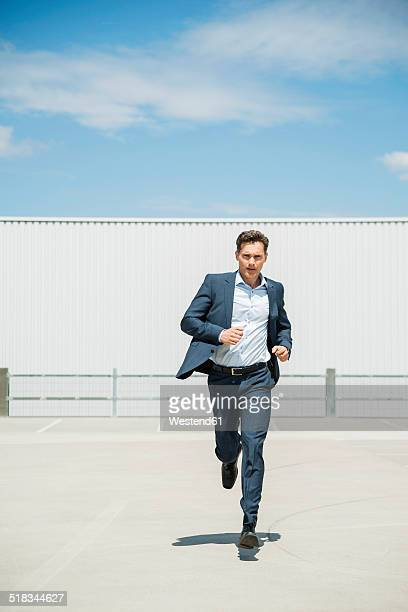 Business man running on parking level