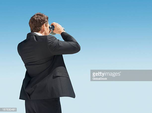 Business man searching for something with binoculars