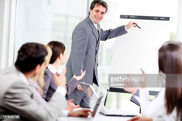 Homme d'affaires montrant le plan de travail sur le tableau à feuilles.