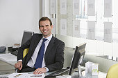 Business man sitting at desk in office smiling portrait