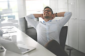 Business man sitting in office and stretched. Business man having break.