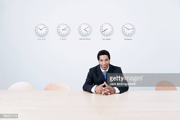 Business man sitting in office in front of clocks on wall
