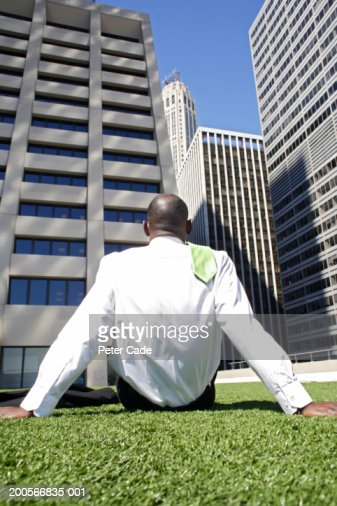 Business man sitting on grass in front of office buildings, rear view : Stock Photo