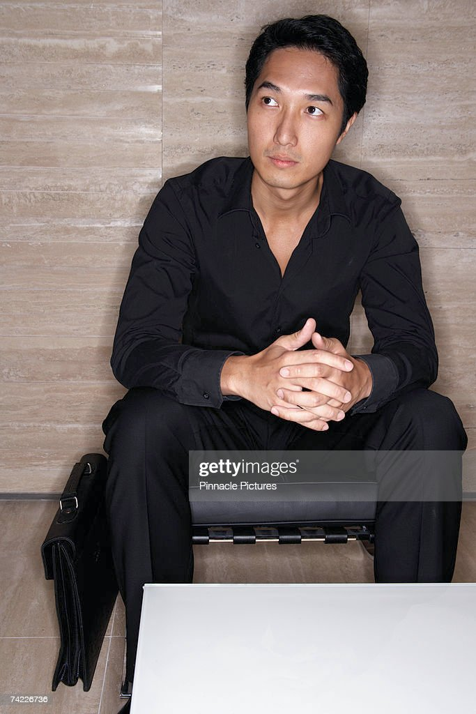 Business man sitting on low chair in office : Stock Photo