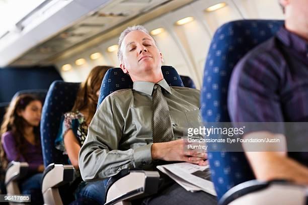 business man sleeping on airplane