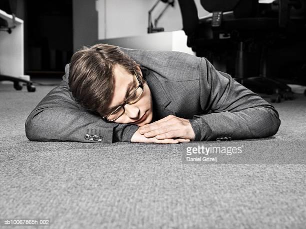 Business man sleeping on carpet in office