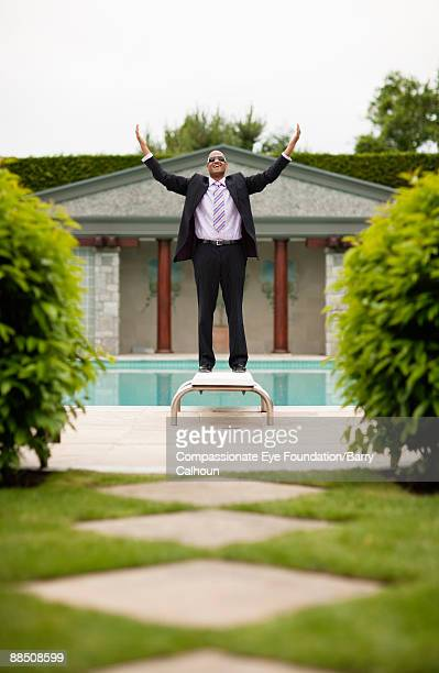 business man smiling in front of pool