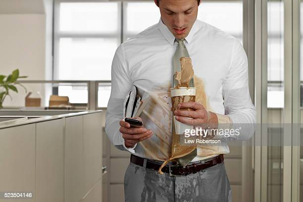 Business man spilling coffee in office