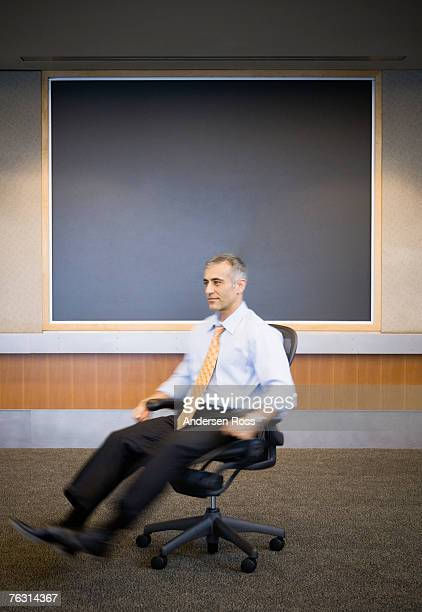 Business man spinning on chair in office