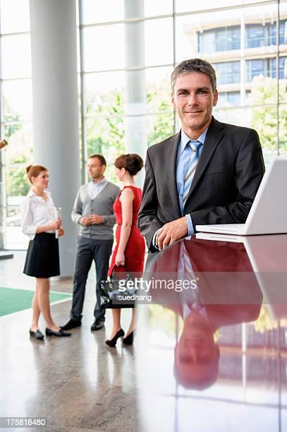 Business man standing against reception desk