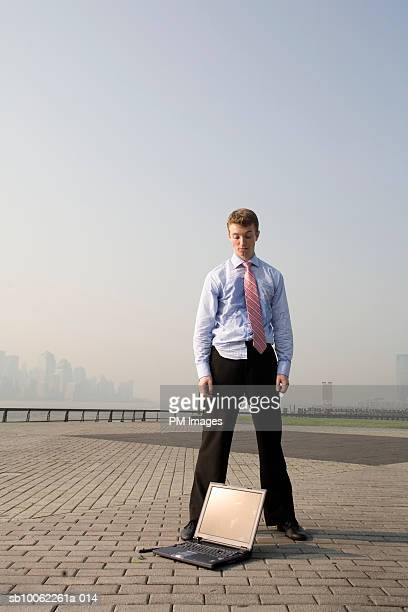 Business man standing by laptop, outdoors
