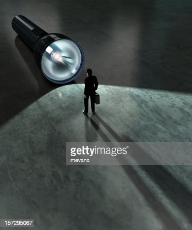 A business man standing in front of a large flashlight