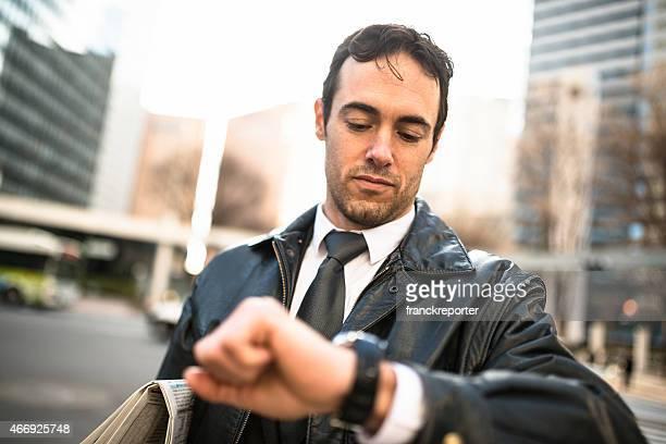 Uomo d'affari in piedi sulla città dell'ora di check-in.