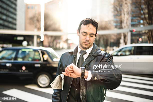 Business man standing on the city checkin the time