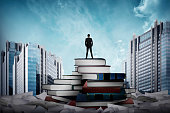 Business man standing on the top of books looking the city