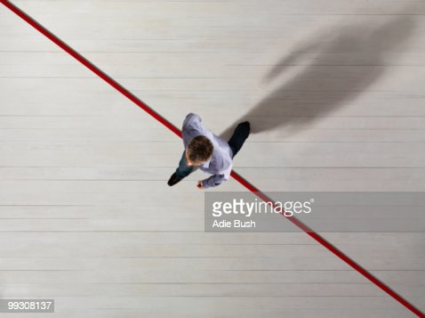 Business man stepping over a red line
