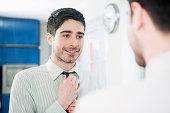 business man straightening tie in mirror