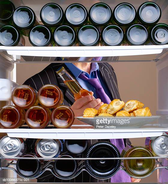 Business man taking beer from fridge