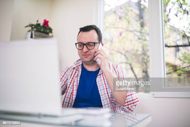 Business man talking on smart phone and look to laptop screen.