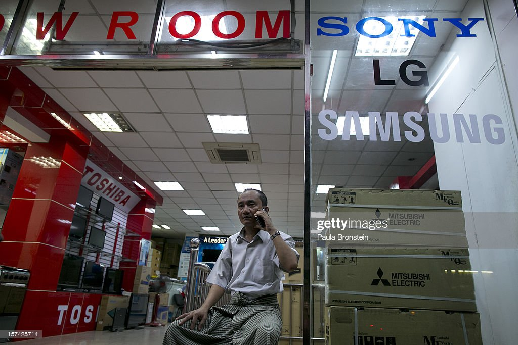 A business man talks on his mobile phone at a new showroom selling a variety of appliances, from TV sets to air conditioners, on November 30, 2012 in downtown Yangon, Myanmar. Business opportunities are expanding in the Southeast Asian country as it emerges from financial isolation. Import restrictions have been eased resulting in many new cars seen on the streets.