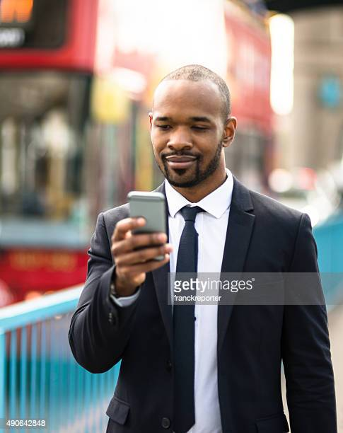 Business man text messaging at tower bridge in London