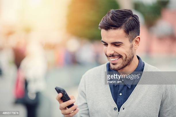 Business man texting on smartphone outside