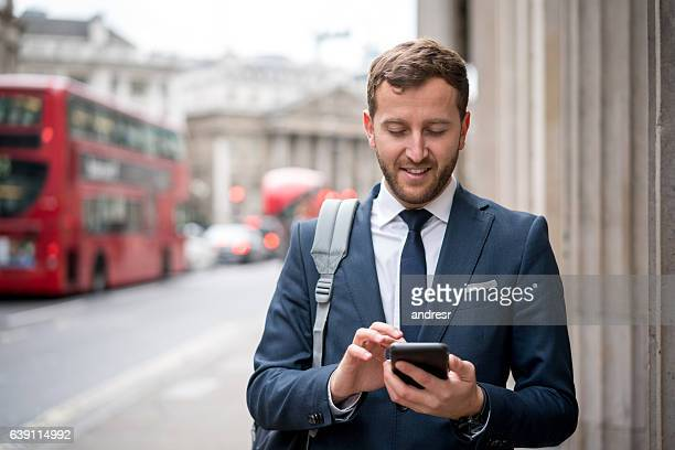 Business man texting on the street