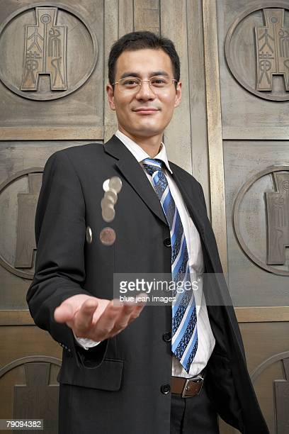 A business man throwing coins.