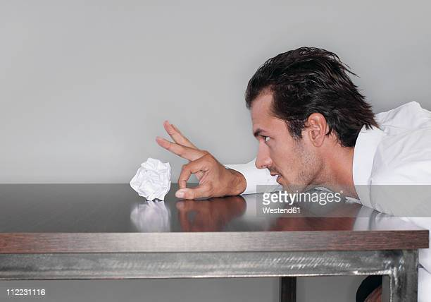 Business man tossing crumpled paper ball