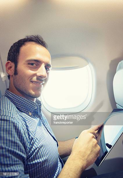 Business man using a digital tablet on the plane