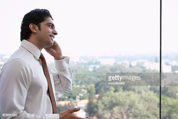 Business man using cell phone, smiling, side view