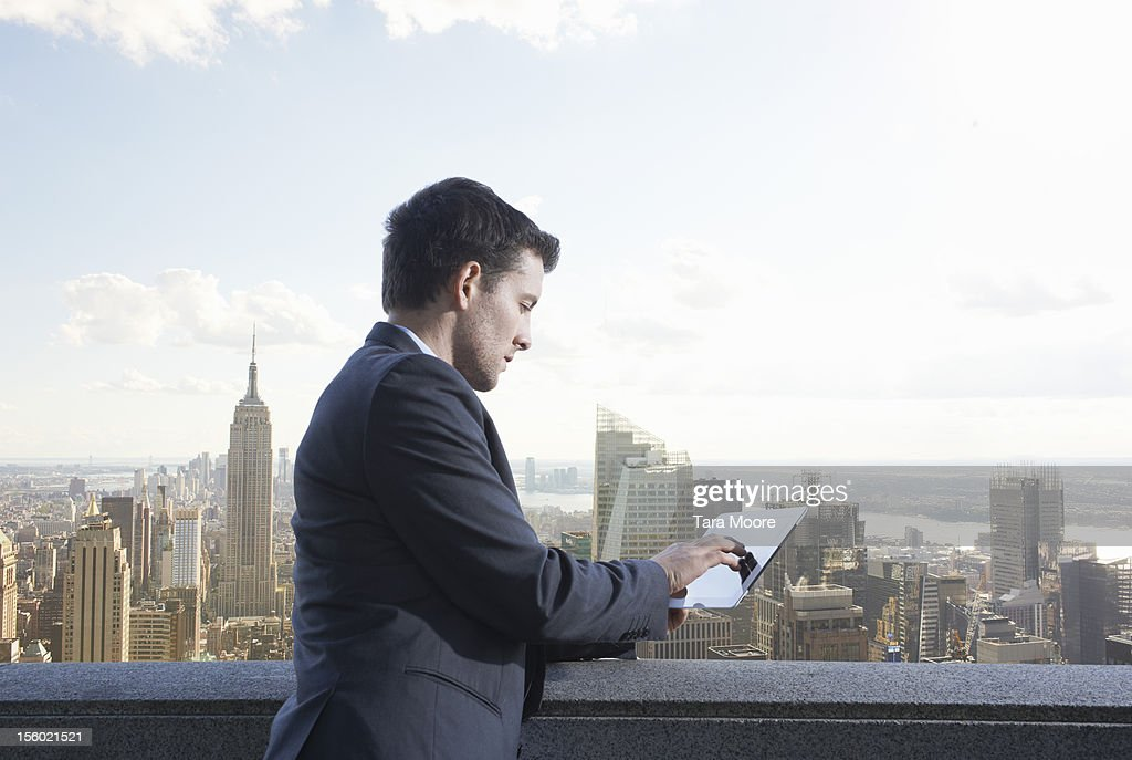 business man using digital tablet next to city sky : Stock Photo