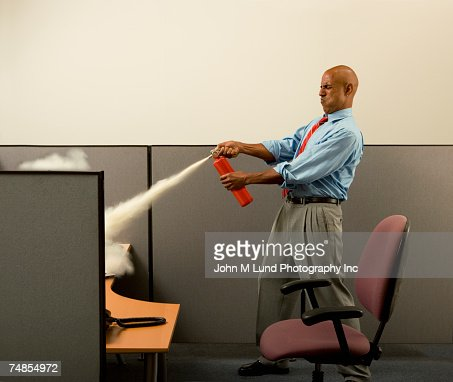 Business man using fire extinguisher on computer in cubicle