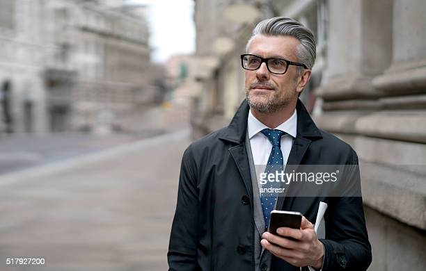 Business man using his cell phone on the street